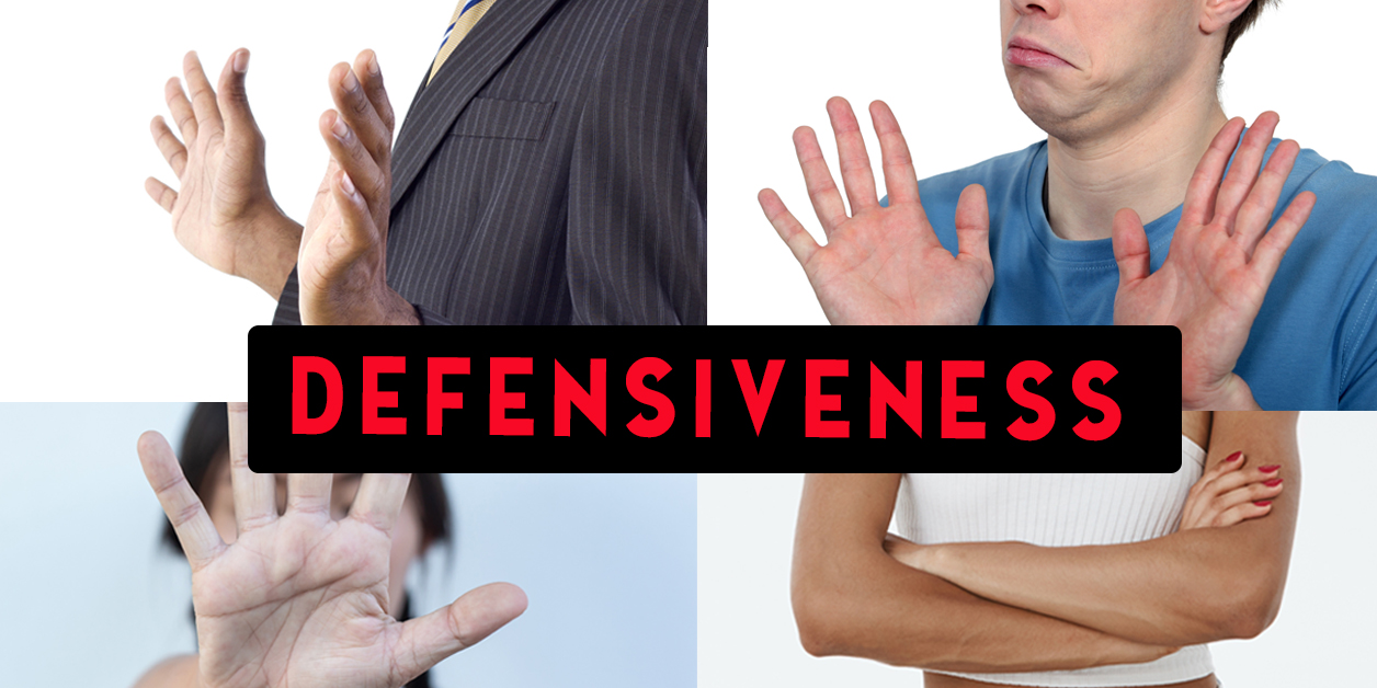 Four body language postures illustrating defensiveness: hands facing outward in front of oneself, crossed arms, hand in front of face